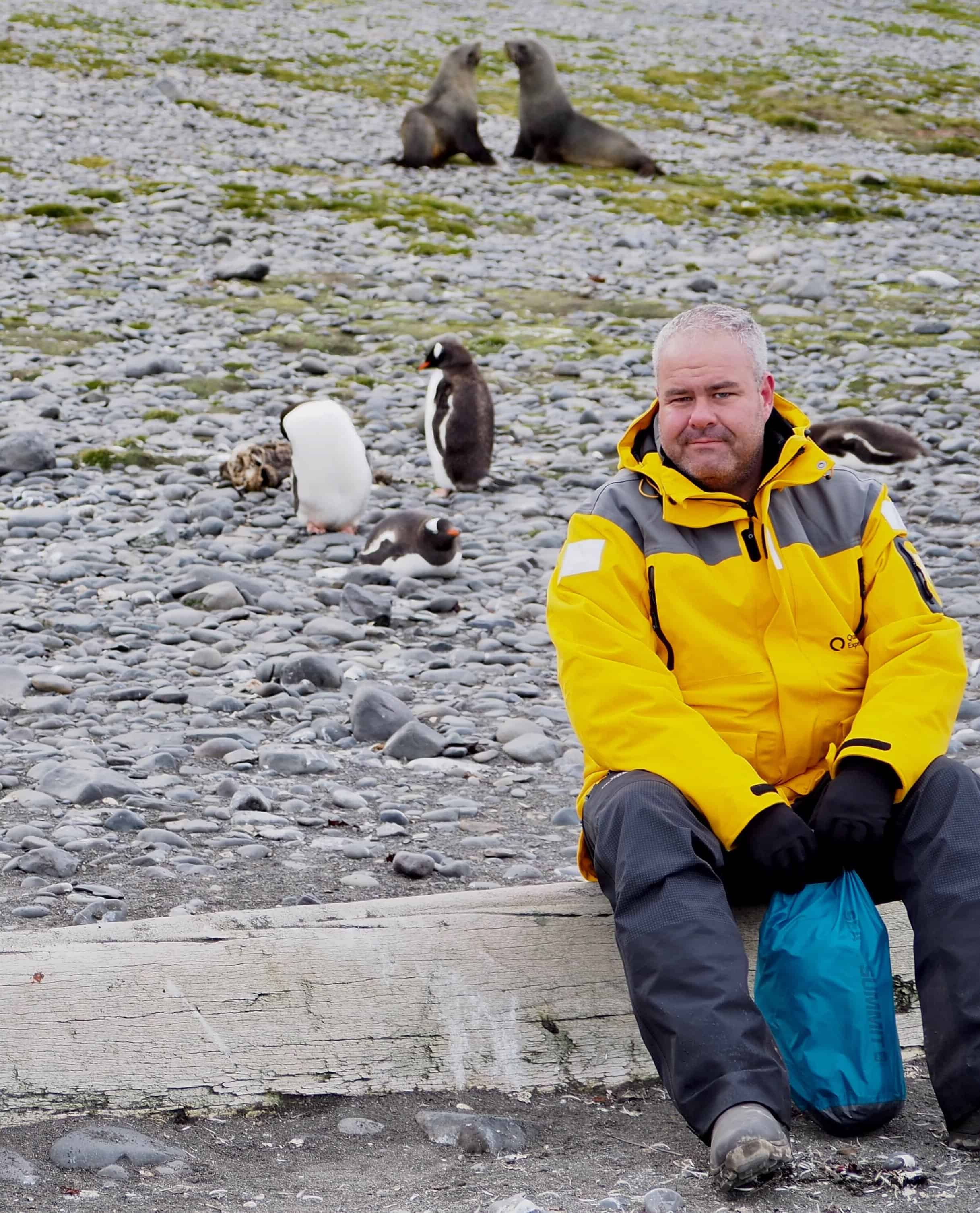 Sitting down with some penguins and seals at Elephant Point, Antarctica