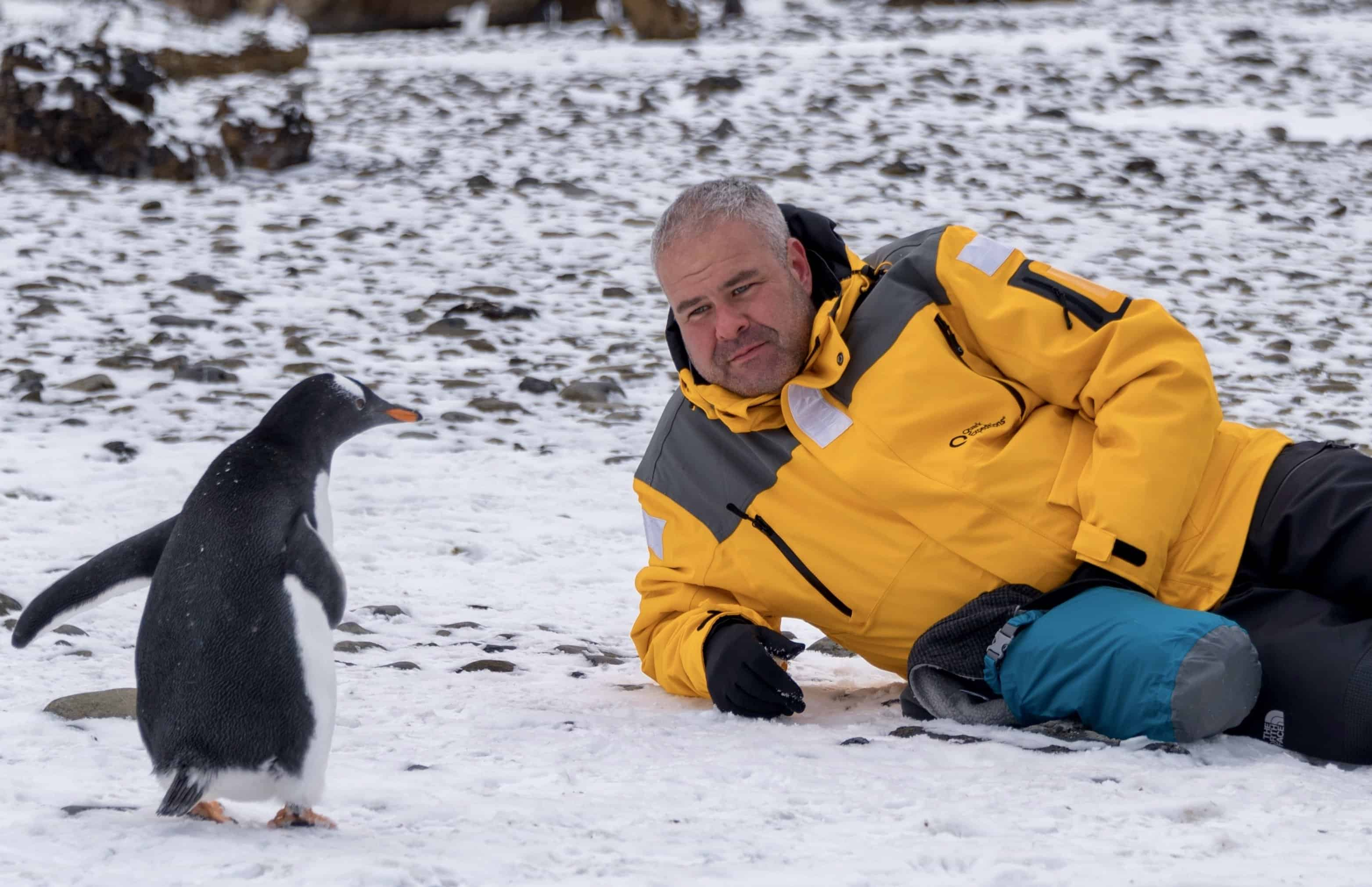 Laying on the snow covered beach of Brown Bluff, Antarctica with a penguin. Antarctica Expedition.
